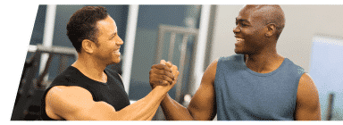Two men clasping hands and smiling in the middle of their workout
