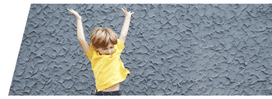 Child jumping and playing in front of a textured wall