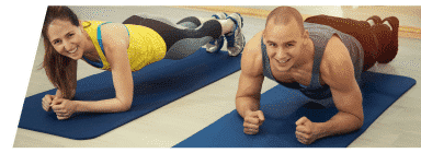 Woman and man performing bridge planks during Pilates class