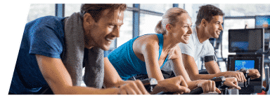Three students cycling on stationary bikes during a spin classes.