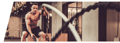 Shirtless athlete using battle ropes for his H.I.I.T. workout.